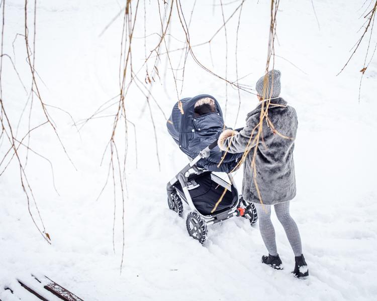 mama spaceruje po śniegu z wózkiem stokke trailz ocieplonym winter kit