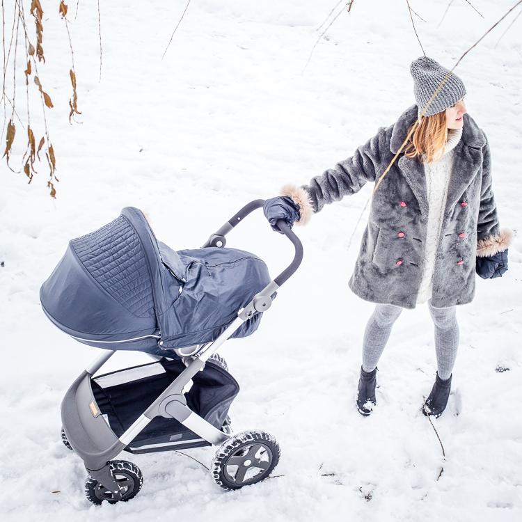 mama spaceruje z córką w wózku trailz oraz winter kit spaceruje w głębokim śniegu ciesząc się z zimy