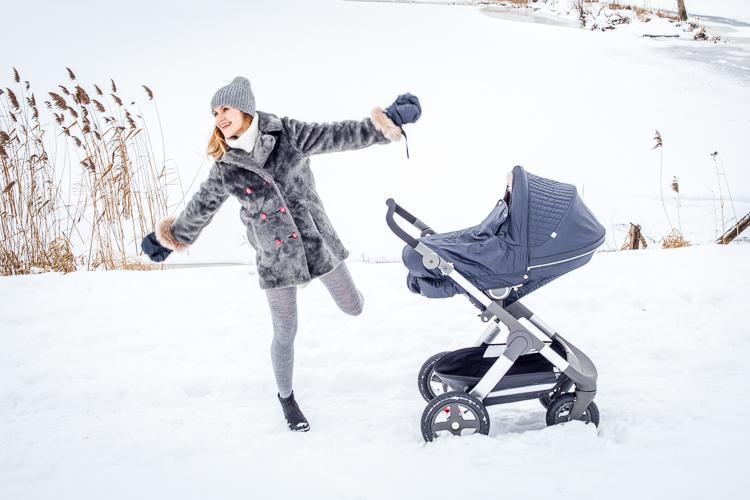 młoda mama cieszy się z zimowego spaceru z wózkiem stokke winter kit