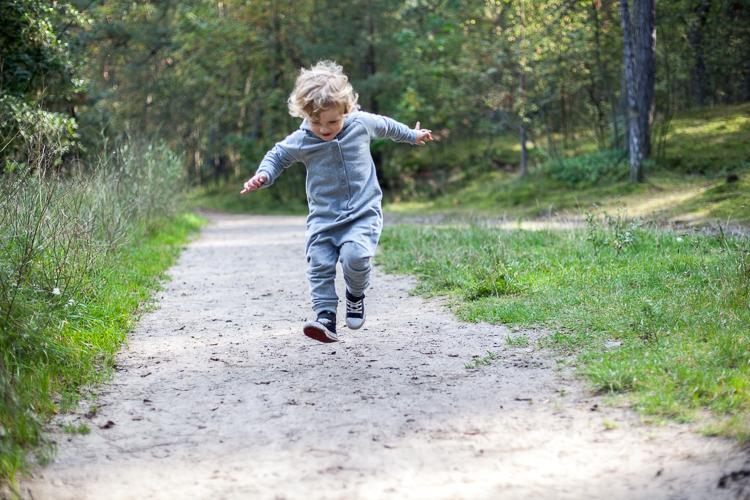 chłopiec ubrany w szary rampers radośnie podskakuje na leśnej ścieżce