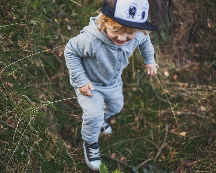 chłopiec ubrany w szary rampers i czapkę z daszkiem spaceruje po mchu na leśnej polanie