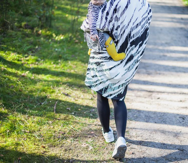 mama w czarno białej sukience Mainio spaceruje z malutką córeczką na rękach po leśnej ścieżce