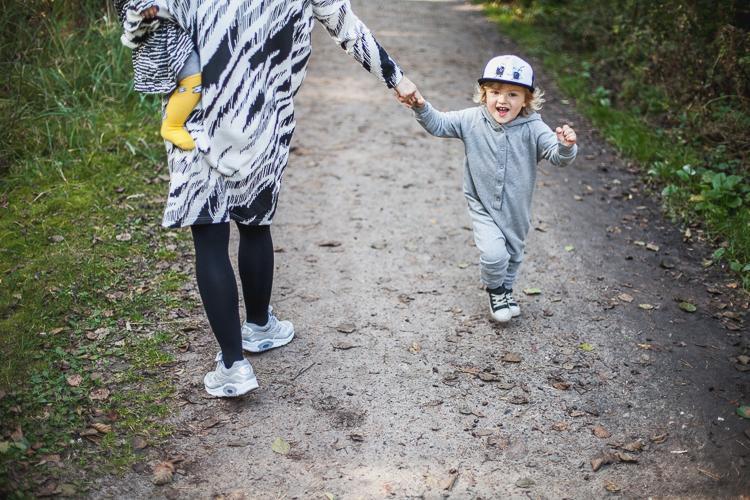 chłopiec ubrany w szary rampers i czapkę z daszkiem spaceruje z mamą i malutką siostrą