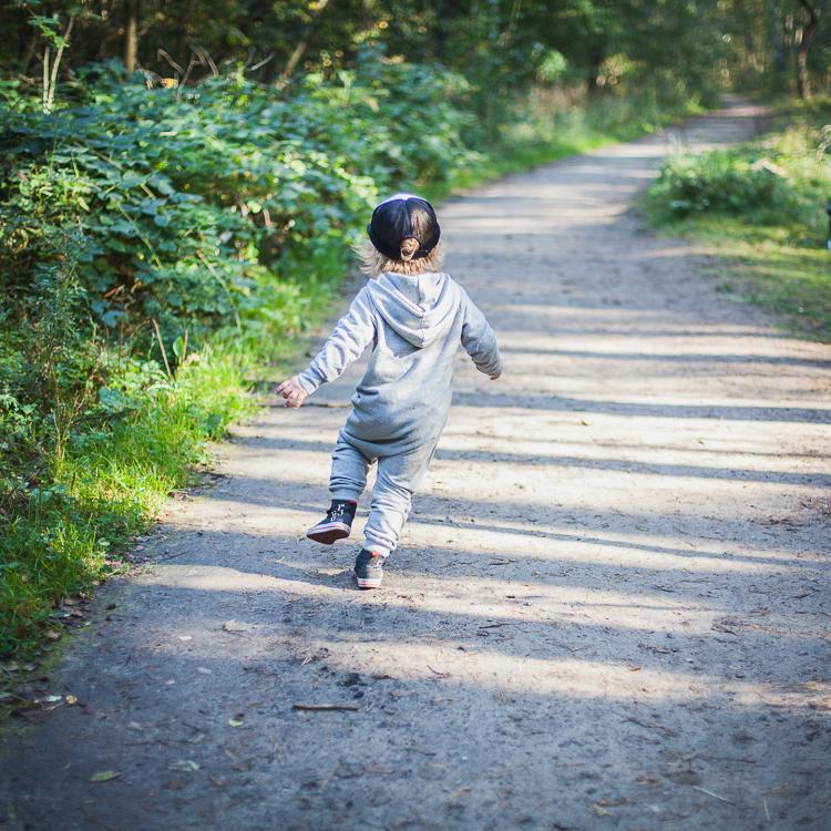 chłopiec ubrany w szary rampers i czapkę z daszkiem biegnie po leśnej ścieżce