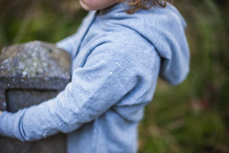 chłopiec ubrany w szary rampers ściska słupek graniczny w lesie