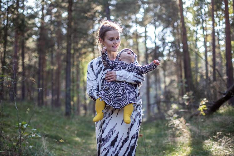 mama w czarno białej sukience Mainio z malutką córeczką na rękach spaceruje jesienią po leśnej ścieżce