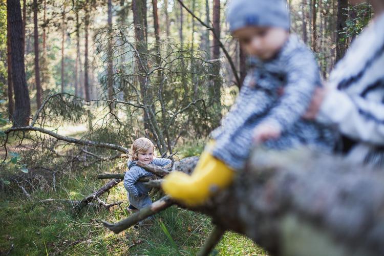 mama w czarno białej sukience Mainio sadza malutką córeczkę w żółtych podkolanówkach z błyskawicami na pniu drzewa