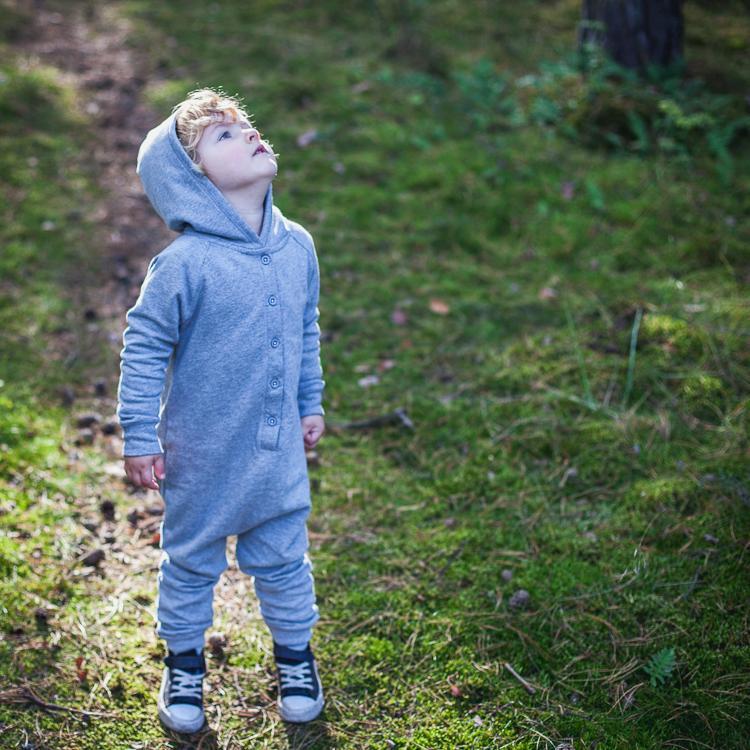 mały chłopiec ubrany w szary rampers z kapturem spaceruje po leśnych ścieżkach