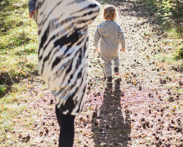 mama z synem i córką spacerują ścieżką leśną oświetloną promieniami jesiennego słońca