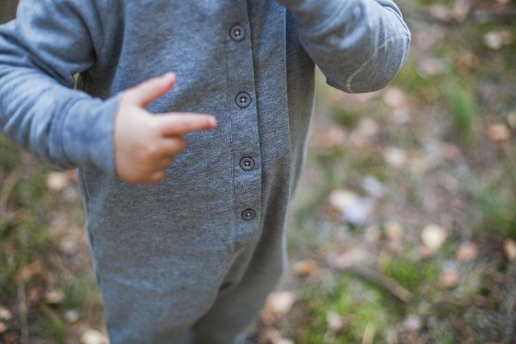 mały chłopiec w szarym rampersie gray label pokazuje guziki