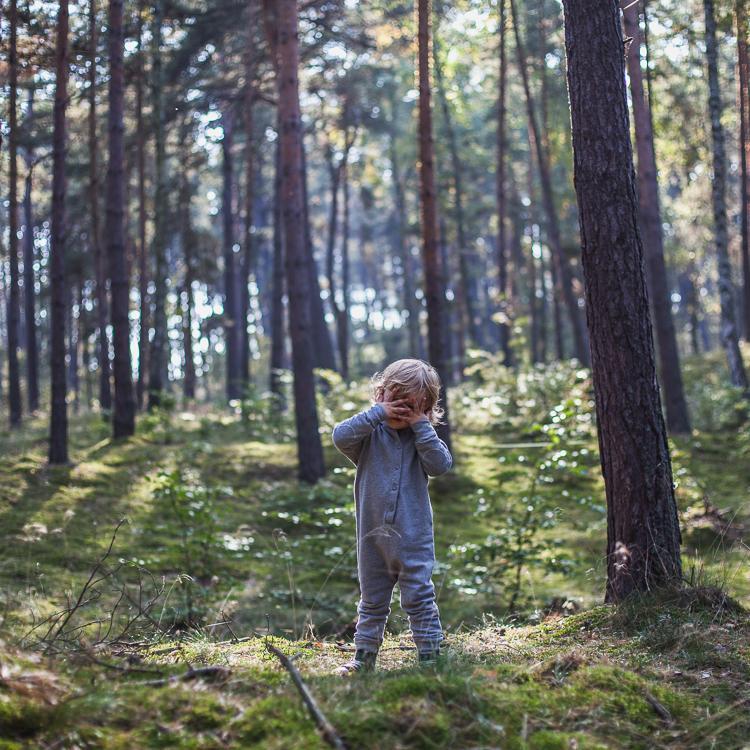 mały chłopiec w szarym rampersie gray label stoi w gęstym sosnowym lesie