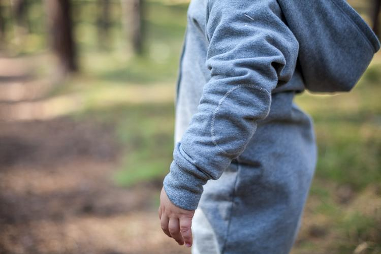 mały chłopiec w szarym rampersie gray label skacze po leśnej ścieżce