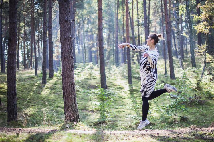 mama ubrana w czarno białą sukienkę mainio bawi się z synem w lesie rzucając z nim szyszkami