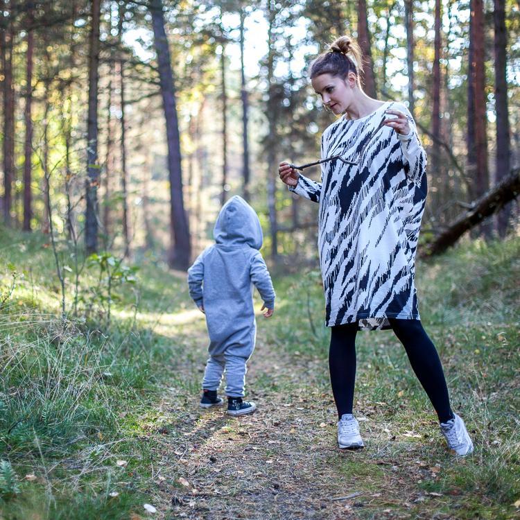 mama ubrana w czarno białą sukienkę i czarne rajstopy spaceruje z synem ubranym w szary rampers z kapturem po lesie