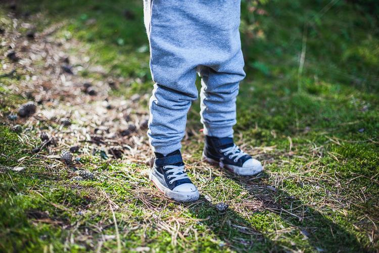 chłopiec w szarym rampersie skacze po grubym mchu