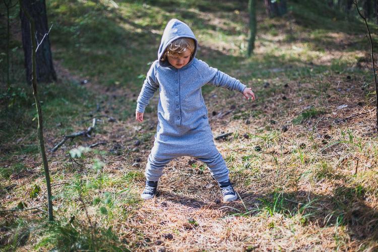 chłopiec ubrany w szary rampers z kapturem radośnie podskakuje na leśnej ścieżce