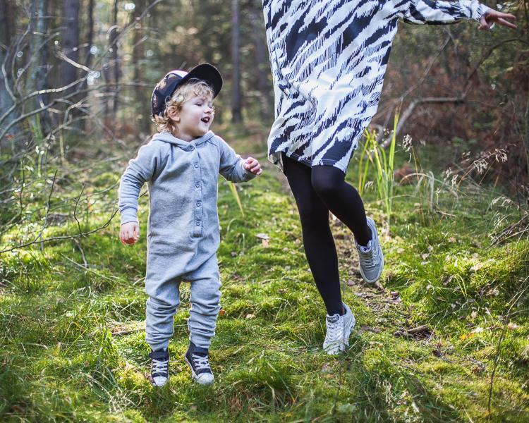 chłopiec ubrany w szary rampers radośnie podskakuje ze swoją mamą na leśnej ścieżce