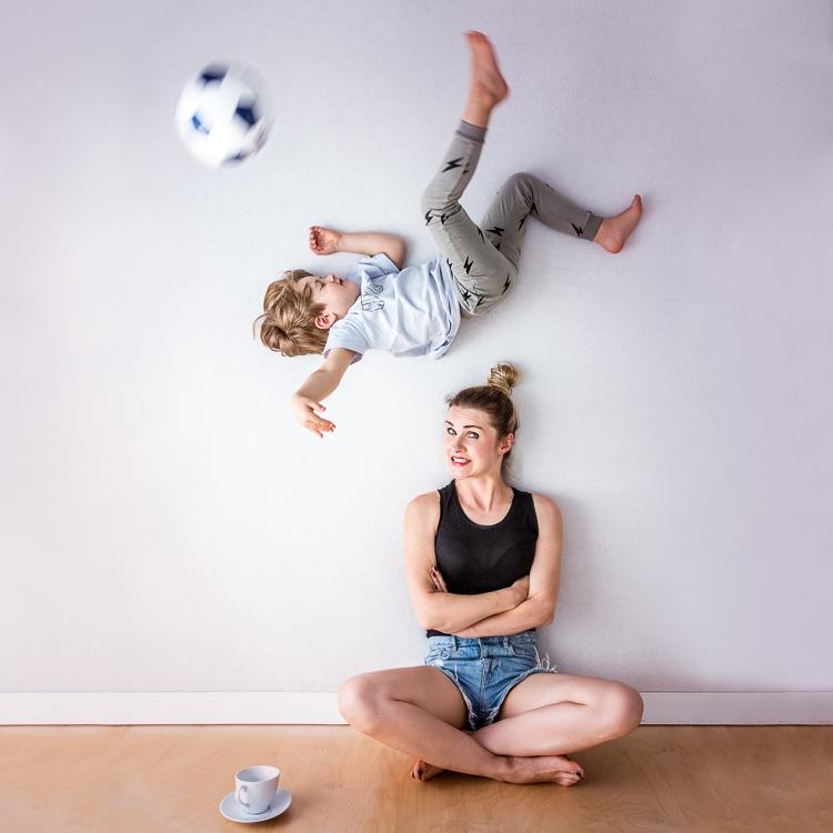 chłopiec w powietrzu kopie piłkę nad głową swojej mamy