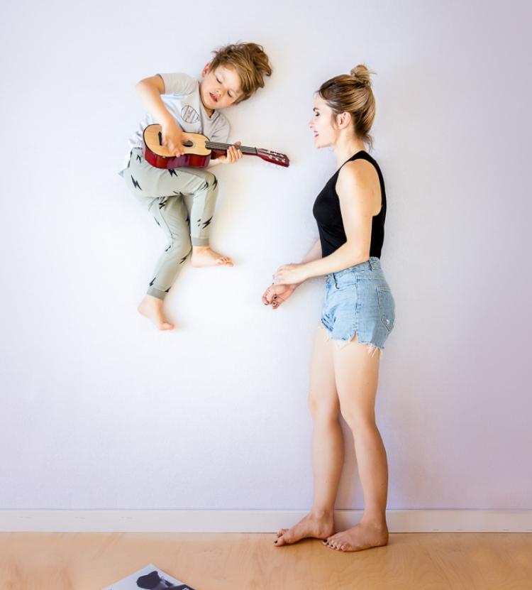 szczęśliwy syn gra mamie na gitarze lecąc w powietrzu
