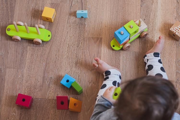 małe dziecko bawi się drewnianą kolejką edukacyjną janod z żyrafą Sophie siedząc na podłodze