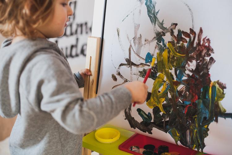 trzylatek rysuje przy małej sztaludze tablicy graffitti janod