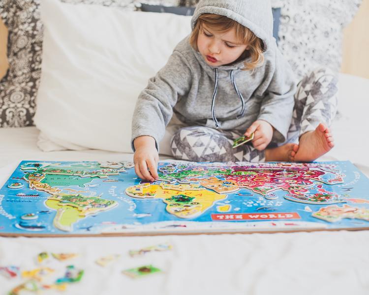 chłopiec bawi się na łóżku układając kolorowe magnetyczne puzzle mapa świata janod