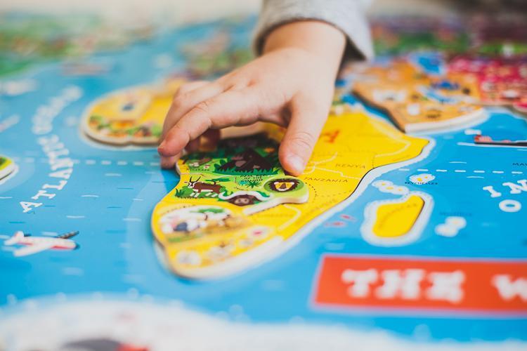 trzylatek układa kraje świata na magnetycznych puzzlach mapa świata janod