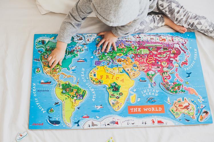 chłopiec testuje układanie edukacyjnej zabawki magnetycznych puzzli mapa świata janod