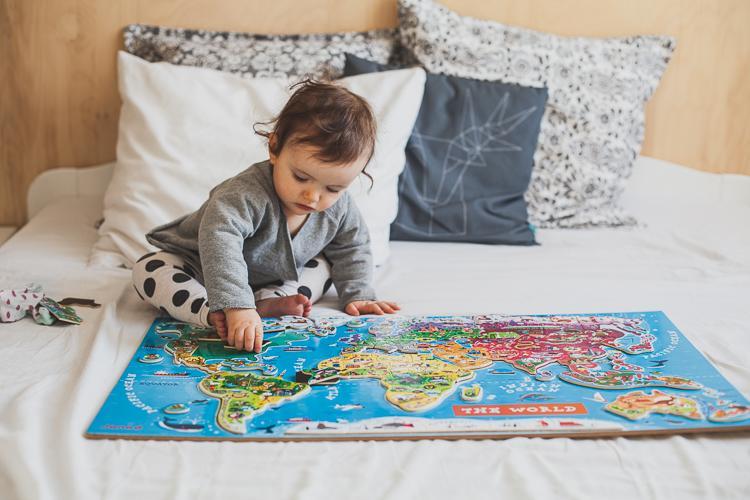 niemowlak bawi się rozkładając magnetyczne puzzle mapa świata janod