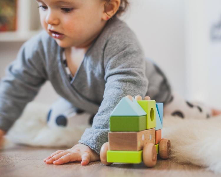 mała dziewczynka bawi się drewnianą kolejką edukacyjną janod z żyrafą Sophie siedząc na podłodze
