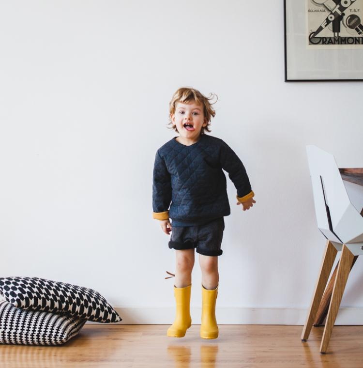 dziecko bawi się w domu ubrane w żółte kalosze bisgaard