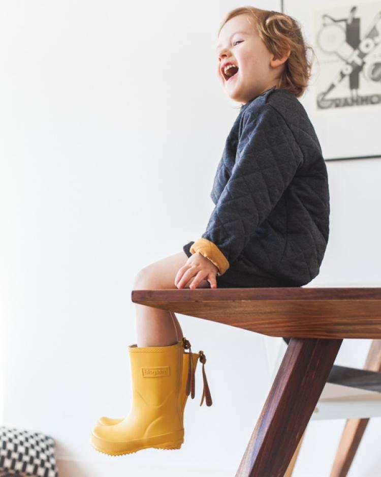 chłopiec w żółtych kaloszach bisgaard i szarej bluzie grain de chic siedzi na drewnianym stole w mieszkaniu