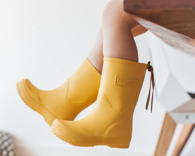 chłopiec w żółtych kaloszach bisgaard bawi się w domu machając nogami
