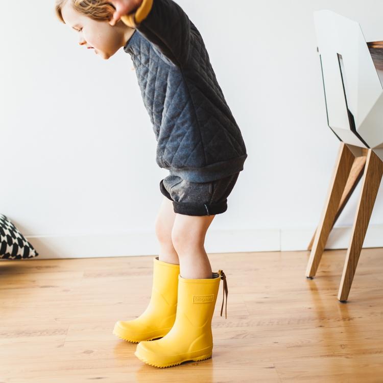 chłopiec w żółtych kaloszach bisgaard bawi się w podróżowanie
