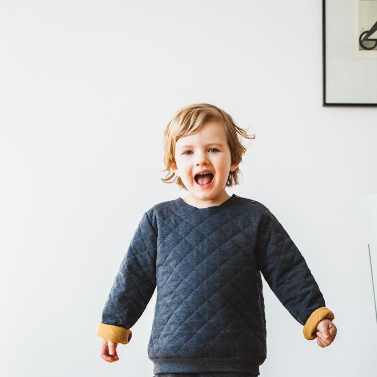 chłopiec w szarej bluzie grain de chic bawi się w mieszaniu z rodzicami
