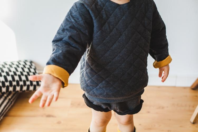 chłopiec w szarej bluzie grain de chic pokazuje rękę podczas kreatywnej zabawy w skakanie